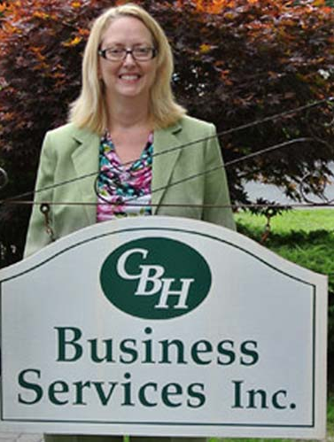 Catherine Bostock-Hudy in front of company sign